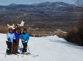 Two Suburban Ski Club skiers on the hill with Sugarloaf moose mascot